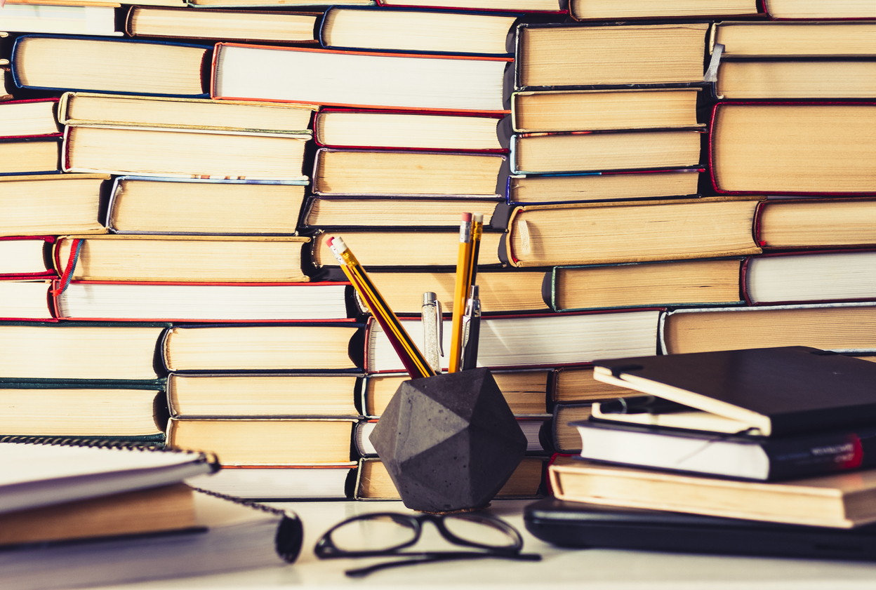 Stack of books, notebook, laptop, glasses in office background for education learning concept top view