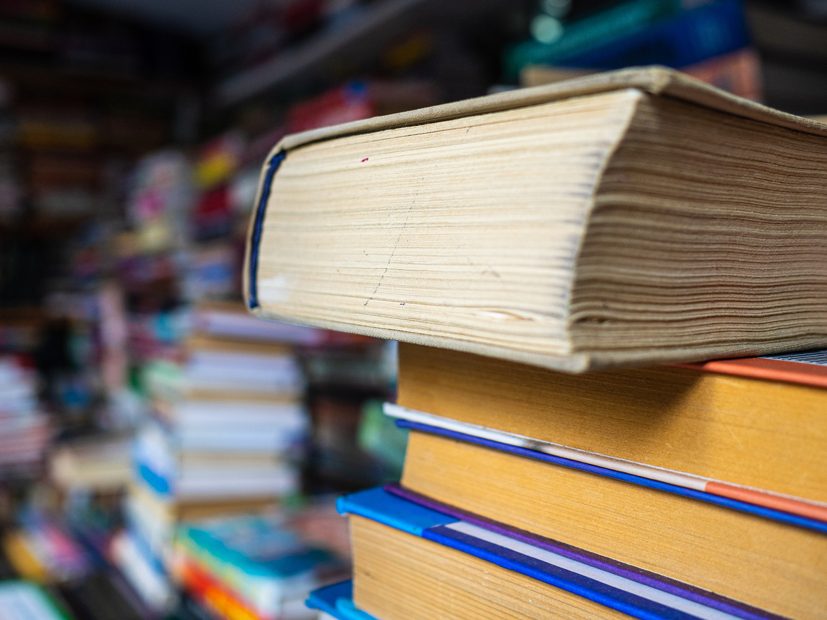 Books with the turned yellow pages stand the friend on the friend in a heap. The shelf with books for sale