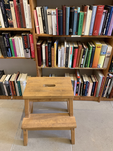 Small stool in front of book wall